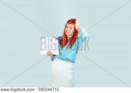 Young Scared Pregnant Woman Having Overweight And Holding Weight Scales Looking At You Camera In Wor