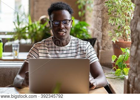 Millennial Black Man Student In Stripped T-shirt Wear Glasses, Watching Educational Webinar On Lapto