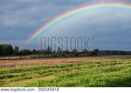 Rainbow Over Stormy Sky. Rural Landscape With Rainbow Over Dark Stormy Sky In A Countryside At Autum