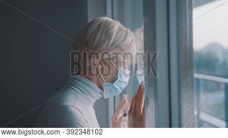 Young Anxious Woman With Face Mask Desperately Looking Through The Window. Mental Health Problem Dur