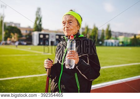 Age Maturity, Active Lifestyle And Wellness. Joyful Retired Woman With Walking Poles And Bottle Of W