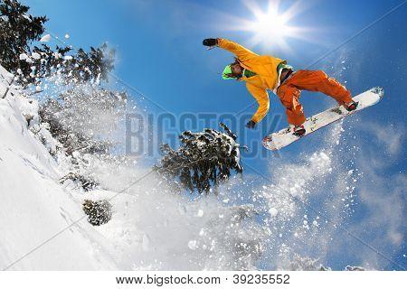 Snowboarder saltar contra el cielo azul