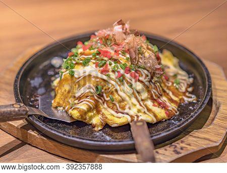 Japanese Okonomiyaki Covered With Katsuobushi Leek Mayonnaise And Bulldog Sauce Served On A Hot Plat