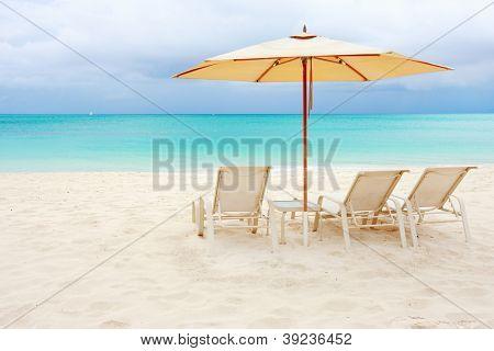 Chairs under umbrella on a stunning Caribbean beach