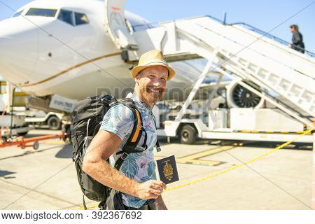 A Young Traveling Man Get In The Plane With Passport On The Landing Strip