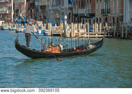 Venice, Italy - September 26, 2017: Gondolier On A Gondola With Tourists On The Grand Canal On A Sun