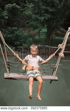 Little boy swinging on a swing over the river