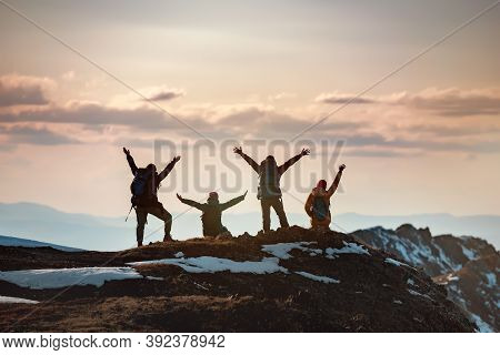 Group Of Happy Hikers Stands With Raised Arms In Winner Poses At Mountain Top And Enjoys Sunset