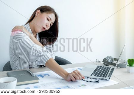 A Successful Business Woman Sitting In The Office Using A Laptop To Work So Hard That It Hurts Her S
