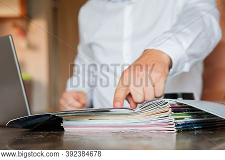 The Manager Looks At The Magazines And The Laptop, In The Foreground Are The Magazines