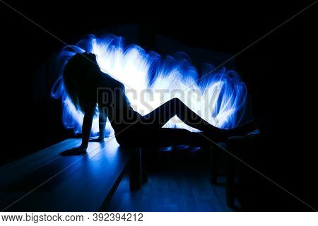 Silhouette Of A Woman With Long Hair, Seated In Profile, Illuminated By White Fiber Optics In The Ba