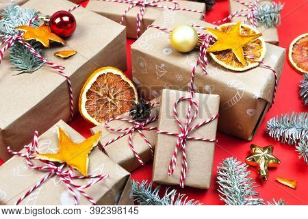 Many Christmas Gift Boxes On Red Background. Holiday Packaging Wallpaper With Christmas Tree Branch,