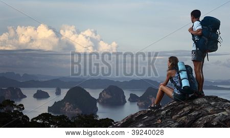 Two hikers with backpacks standing on top of a mountain and enjoying great view to surrounding islands