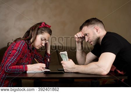 A Man Holds Money And Watches His Wife Calculate The Budget. The Difficulties Of A Young Family, The