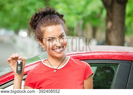 Happy Woman Driver Showing Car Keys And Leaning On Car Door Wearing Red Shirt Outdoors, Outside In S