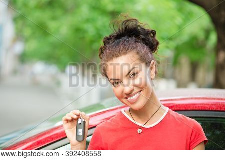 Young Beautiful Black Woman Driver Holding Showing Car Keys Her New Car Wearing Red Shirt Outdoors,