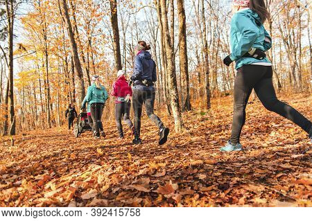 Woman Group Out Running Together In An Autumn Park They Run A Race Or Train In A Healthy Outdoors Li