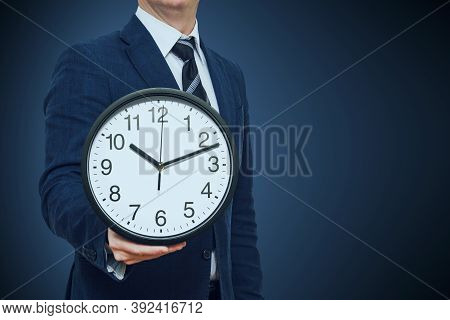 Clock In Businessman Hand. Businessman With A Clock In A Hand. Businessman With Clock In Time Concep