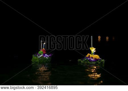 Two Kratong Float On The Night Liquid With Glare. Loy Kratong Festival In Thailand.