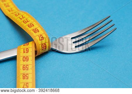 Measuring Tape With Fork On Blue Background. Concept Of Weight Loss. Weight Management. Healthy Life