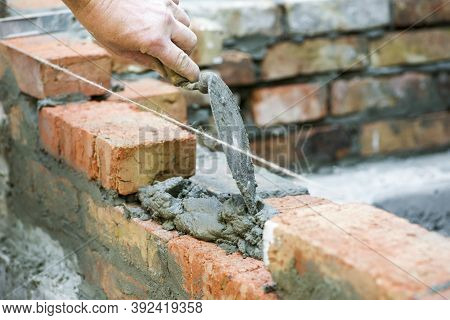 Bricklayer Worker Installing Brick Masonry On Exterior Wall. Professional Construction Worker Laying