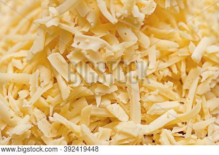 Grated Cheese For A Background. A Very Close View Of Shredded Cheese