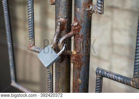 Locked Lock Old Rusty Metal Door Close Up. Antique Slide Steel Locked Shutter Door. The Lock, On The