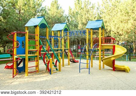 Colorful Playground On Yard In The Park. Children's Playground In The Park. Playground Toy Set In Pu