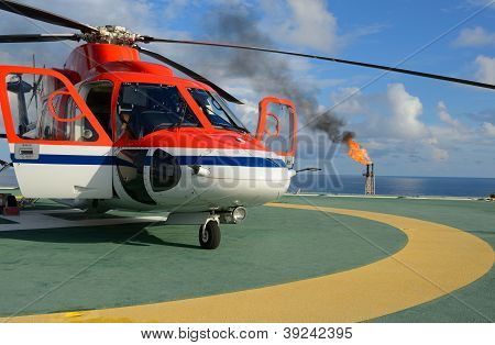 The helicopter park on oil rig to pick up worker with gas flare and blue sky backgroung poster