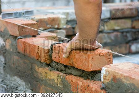 Building Brick Block Wall On Construction Plant. Worker Builds A Brick Wall In The House. Constructi