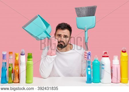 Upset Tired Husband Wears Pink Rubber Gloves, Carries Broom And Scoop, Takes Break After Sweeping Fl