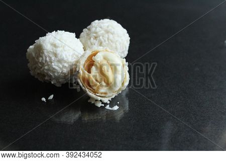 One Two Three A Few White Candies In A Coconut Sprinkle Like Raffaello On A Glossy Black Background