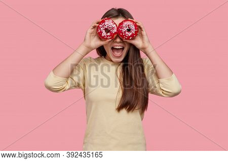 Studio Shot Of Happy Dark Haired Woman Covers Eyes With Two Red Donuts, Being In High Spirit, Wears