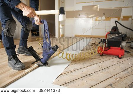 A Male Worker Install Wood Floor On A House