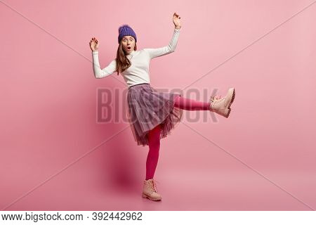 Frightened Woman Afraids Of Falling On Slippery Road, Raises Hands And Legs, Wears White Jumper And