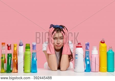 Horizontal Shot Of Dissatisfied Young Housemaid Keeps Hands On Head, Cries Desperately, Being Tired