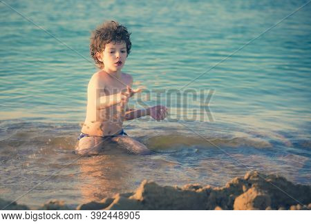 Cute Curly Male Kid Playing Game At The Beach. Little Boy Play With Sand On Summer Beach. Funny Game