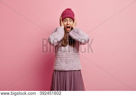Waist Up Shot Of Scared Frightened Young Woman Keeps Hands On Head, Stares With Bugged Eyes, Screams