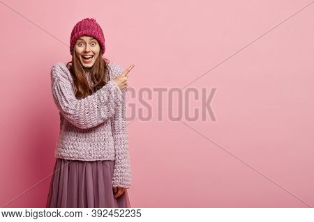 Studio Shot Of Pleased Woman With Positive Smile, Points With Fore Finger, Wears Knitted Sweater And