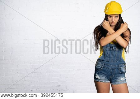 Teenager Clothes In Dungarees With Short Legs. Yellow Protective Helmet. A Woman As A Construction W