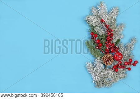 Christmas Composition Of Snowy Fir Branches And Red Berries On A Blue Background. Winter Festive Nat