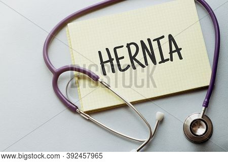On A Purple Background A Stethoscope With Yellow List With Text Hernia