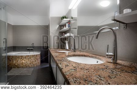 Modern Bathroom In Cool Style With Glass Shower And Bathtub Lined With Red Stones And Marble.