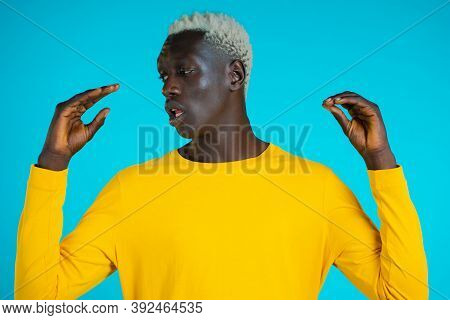African American Bored Man Showing Bla-bla-bla Gesture With Hands And Rolling Eyes Isolated On Blue