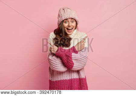 Happy Pleasaed Woman With Dark Curly Hair, Smiles Positively, Crosses Arms Over Chest, Being Confuse