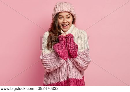 Studio Shot Of Joyful Pretty Woman Wears Loose Knitted Pullover And Hat, Being In Good Mood After Wa
