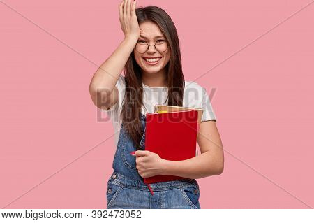 Pleased College Student Keeps Hand On Head, Smiles Broadly, Holds Textbook, Remember About Important