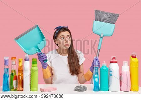 Tidyness And Cleaning Concept. Attractive Dark Haired Woman Wears Headband, Has Upset Look, Carries