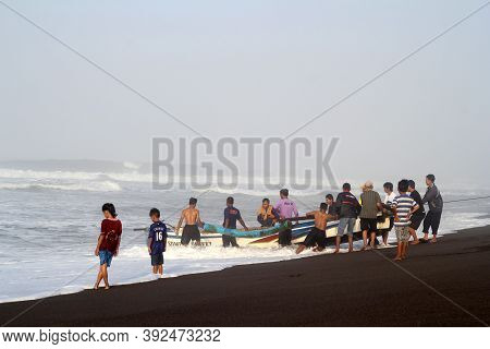 Yogyakarta, Indonesia - September 20, 2017: Some People Working Together Pull Fishing Boats To The B