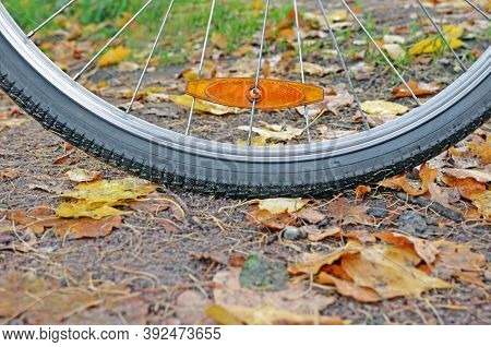 Fragment Of Bicycle Wheel With Orange Reflector On Spokes On Gravel Path With Fallen Leaves In Fall